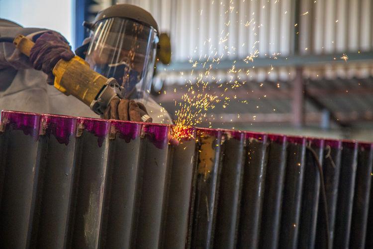 Worker welding metal at workshop