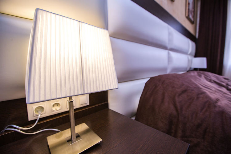 Illuminated electric lamp on side table in bedroom at home