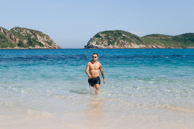 Water Sea Shirtless Land Beach One Person Sky Leisure Activity Nature Lifestyles Beauty In Nature Standing Day Rock Real People Young Adult Rock - Object Men Outdoors Ankle Deep In Water