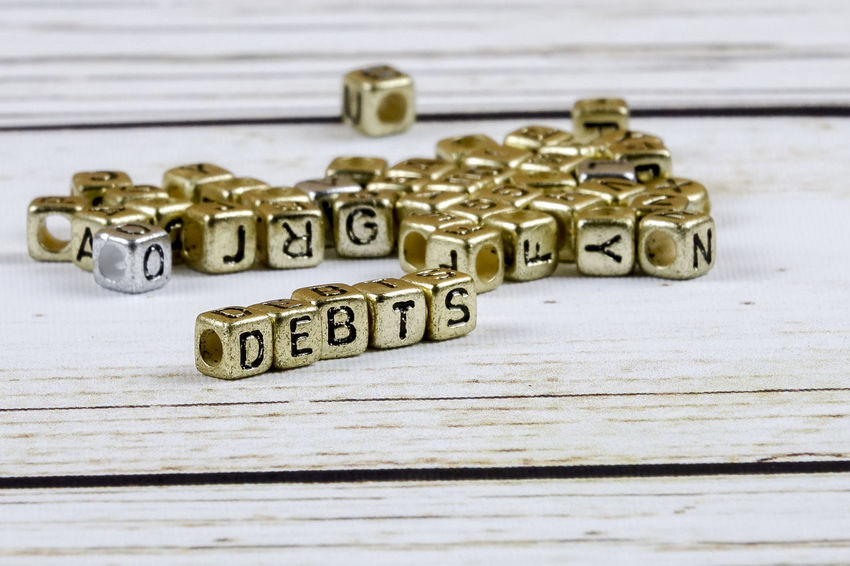 DEBT CONCEPT WITH GOLD DICE ON A WOODEN TABLE Capital Letter Close-up Communication Credit Card Debt Crisis High Angle View Indoors  Key Large Group Of Objects Letter No People Number Pattern Selective Focus Single Word Still Life Table Text Toy Toy Block Western Script Wood - Material