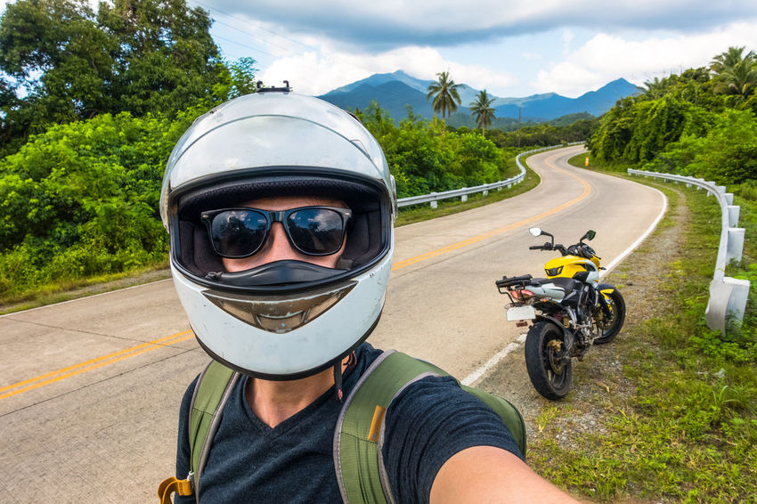 motorcycle and rider in helmet taking selfie on side of island road Bacpacker Island Adventure Island Life Island Vibes Island View  It's More Fun In The Philippines Motorbike Motorcycle Motorcycle Helmet Motorcycle Rider Motorcycle Trip Motorcyclist Palawan Philippines Rider Road Shoulder Road Trip Safety Selfie Side Of The Road Speeding The Philippines Touring Windy Road ısland View