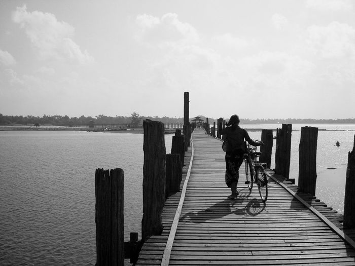 Rear view of woman walking with bicycle on wooden footbridge over river against sky