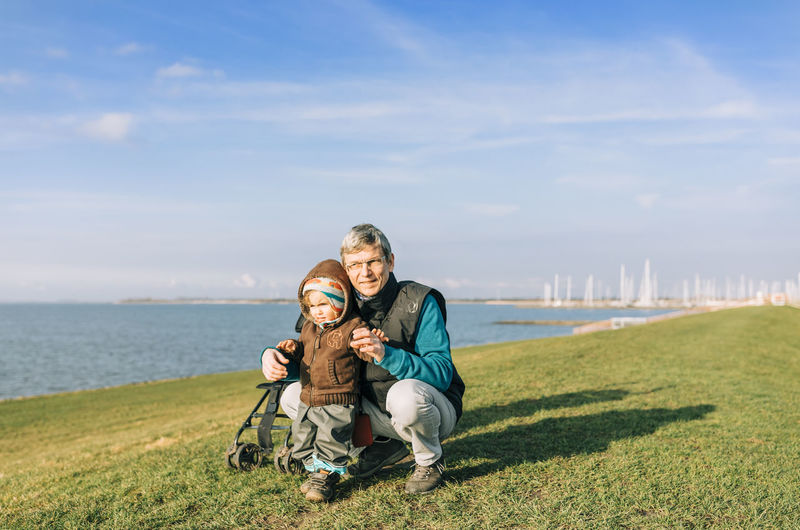Man with toddler girl on dyke of IJsselmeer – Hindeloopen, Netherlands, Europe Males  Grandfather Grandchild Granddaughter Multi-generation Family Family❤ Offspring Generations Generation Gap Crouching Holding Hands First Steps Care Love Netherlands Caucasian Vacations Dyke  Ijsselmeer Lake Mature Men Child Toddler  Toddlerlife Exploring Togetherness Emotion Smiling Looking At Camera Sky Water Grass Happiness Family Adult Portrait Bonding Nature Two People Day Positive Emotion Females Sea Outdoors