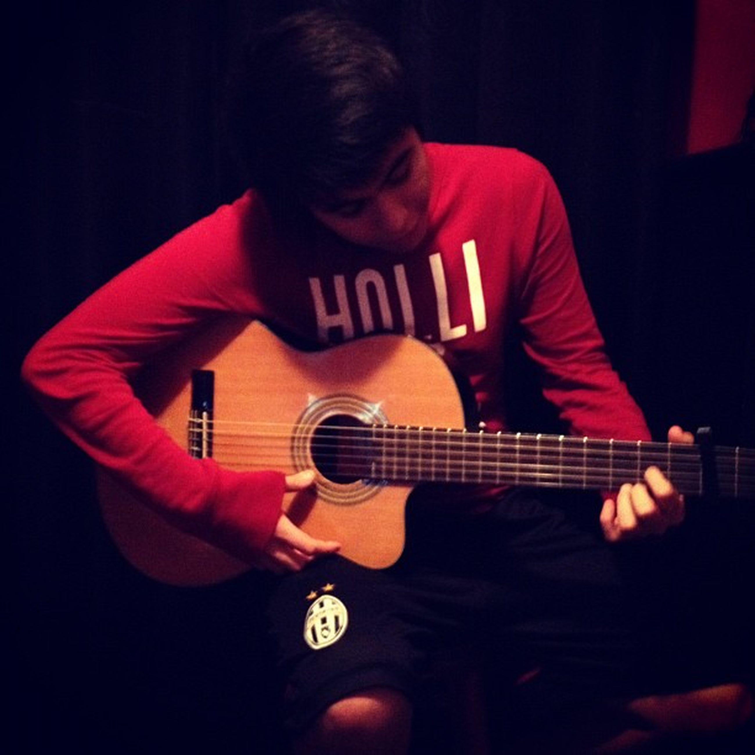 indoors, holding, playing, music, guitar, lifestyles, musical instrument, leisure activity, arts culture and entertainment, technology, casual clothing, wireless technology, communication, night, skill, men, childhood, hobbies