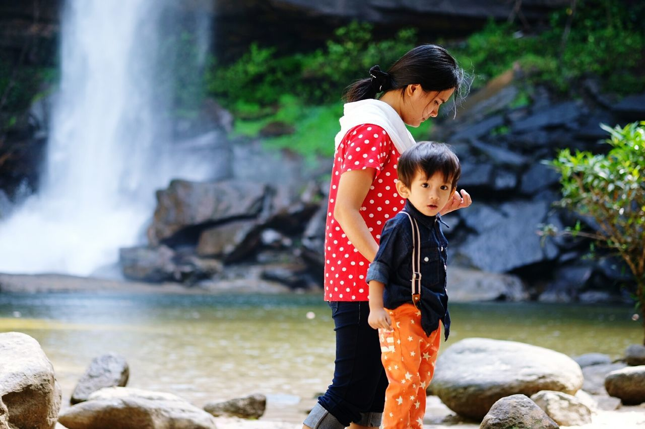 Portrait Of Cute Boy With Mother Against Waterfall