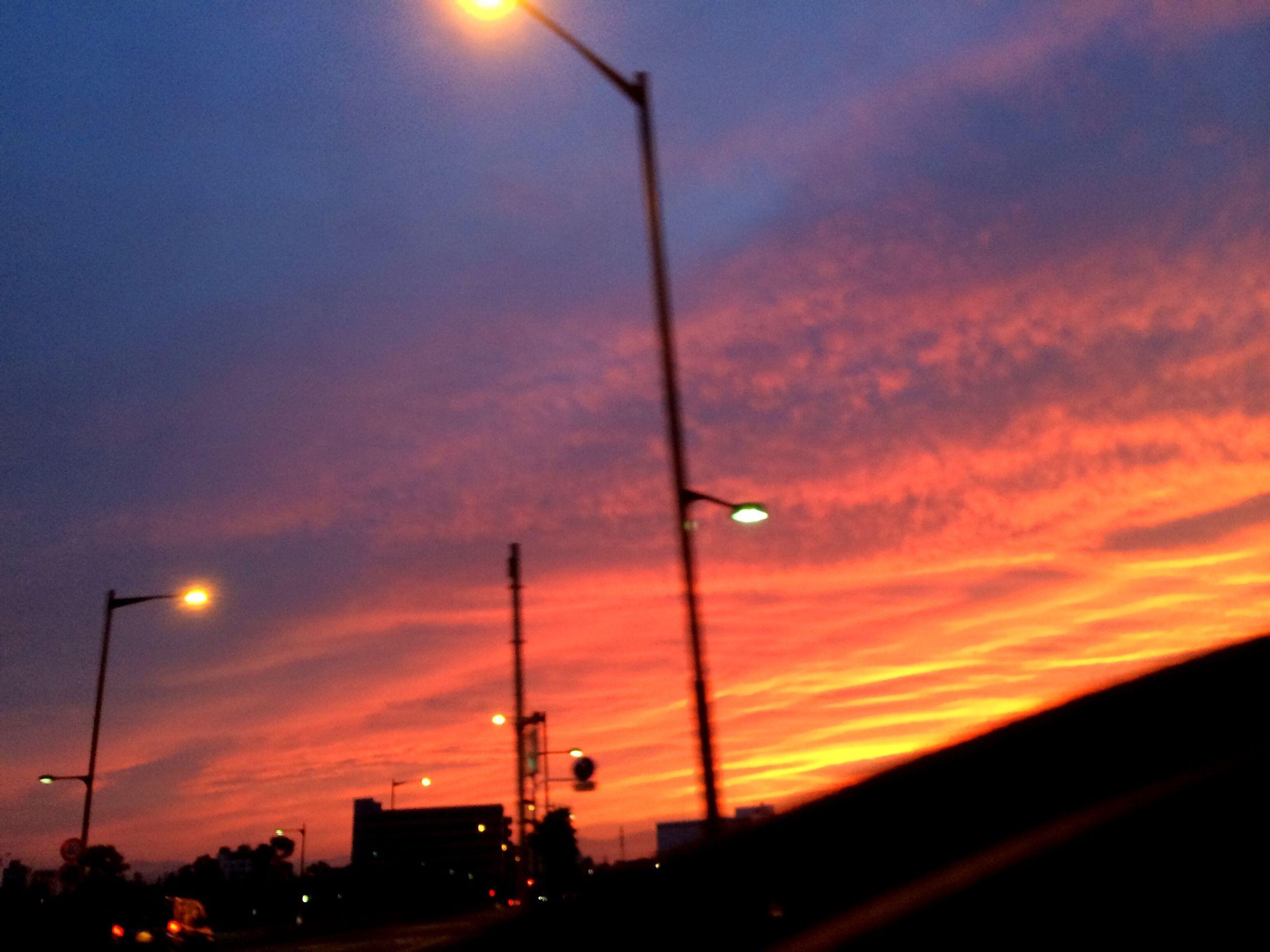 sunset, street light, silhouette, sky, orange color, low angle view, cloud - sky, lighting equipment, dramatic sky, transportation, cloud, car, electricity pylon, dusk, power line, beauty in nature, cloudy, nature, scenics, illuminated