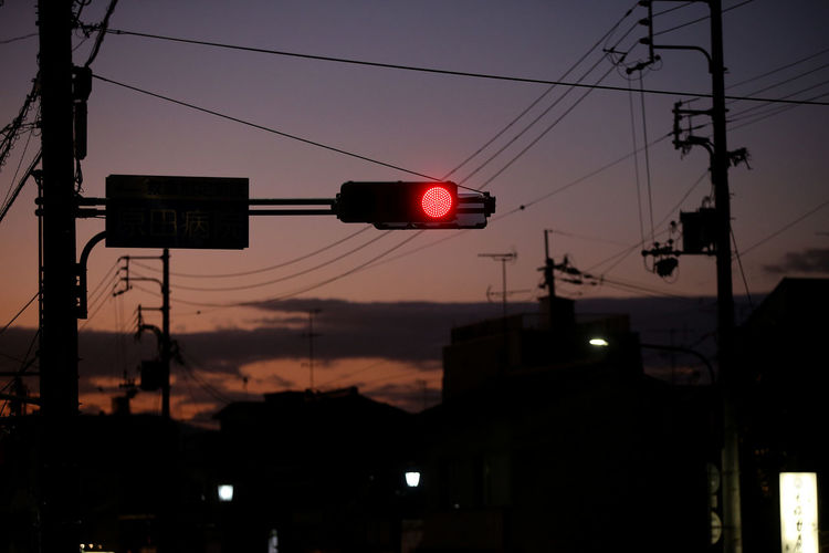 Low angle view of road signal against sky at sunset