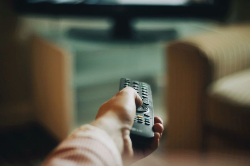 Cropped hand of woman holding remote control