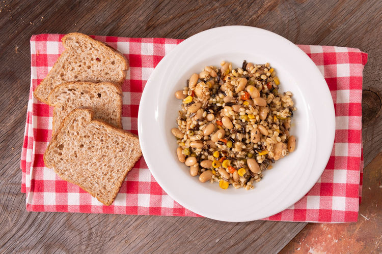 Spelled, chickpea, tuna and corn salad arranged on rustic table with bread Bread Breakfast Breakfast Cereal Brown Bread Checked Pattern Dietary Fiber Directly Above Eating Utensil Food Food And Drink Freshness Fruit Healthy Eating High Angle View Indoors  Meal No People Oats - Food Ready-to-eat Seed Still Life Table Wellbeing