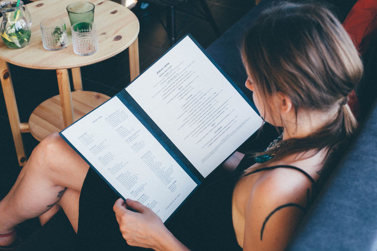 High angle view of young woman reading menu while sitting on sofa at cafe