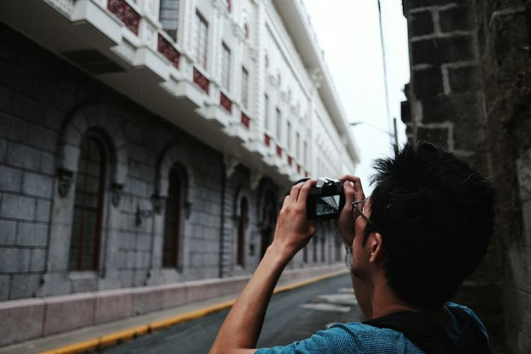 Side View Of Young Man Photographing Building Through Camera While Standing On Street
