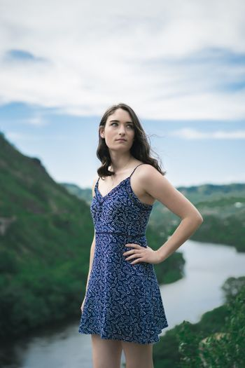 Portrait of beautiful young woman standing against sea