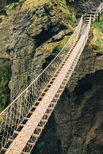 Carrick-a-Rede Rope Bridge Northern Ireland Rope Bridge Bridge Built Structure Connection Day High Angle View Mountain Nature No People Outdoors Rock Scenics - Nature Solid Stone Wall Tourism Travel Travel Destinations Go Higher