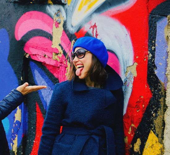 Cheerful woman sticking out tongue against colorful graffiti wall