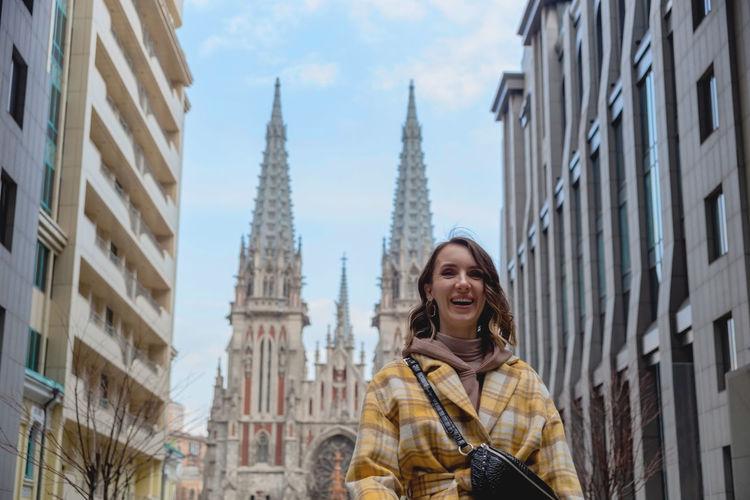 Happy millenial woman in a yellow coat in european city