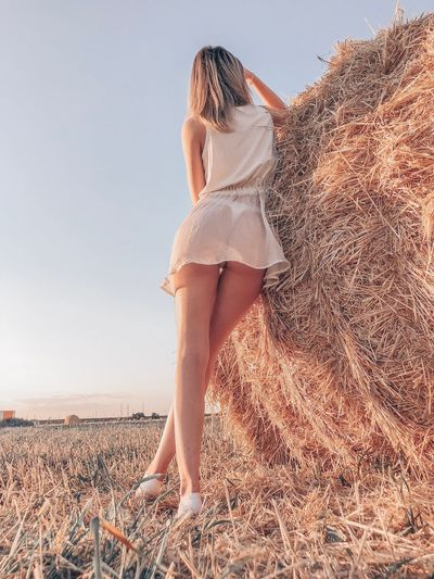 Low angle view of woman standing by hay against sky