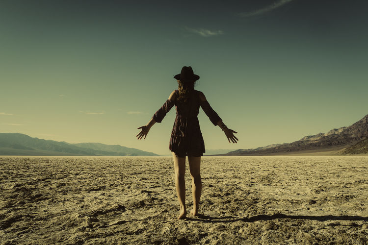 Full Length Of Woman With Arms Outstretched Standing At Field Against Sky