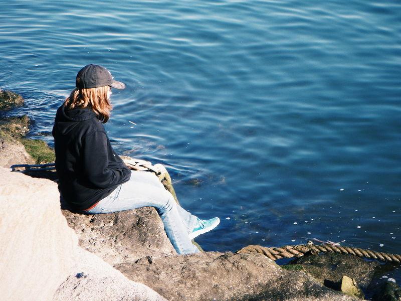 Blue Wave Showcase April Seat Rocks And Water Dirt Bushes Rocks Rock Blue Traveler Girl Girl Sitting Sitting Outside Sitting Sitting Alone Alone Water Ocean Shore Hat Rope Thinking Sitting On Rock Sitting On A Rock Outside