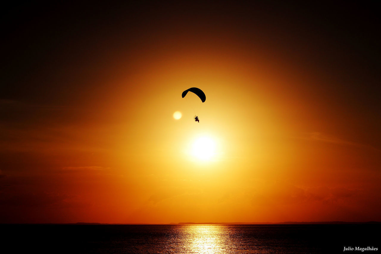sunset, sea, water, nature, scenics, silhouette, tranquil scene, adventure, beauty in nature, sun, reflection, horizon over water, tranquility, parachute, sky, one person, outdoors, extreme sports, paragliding, day, people