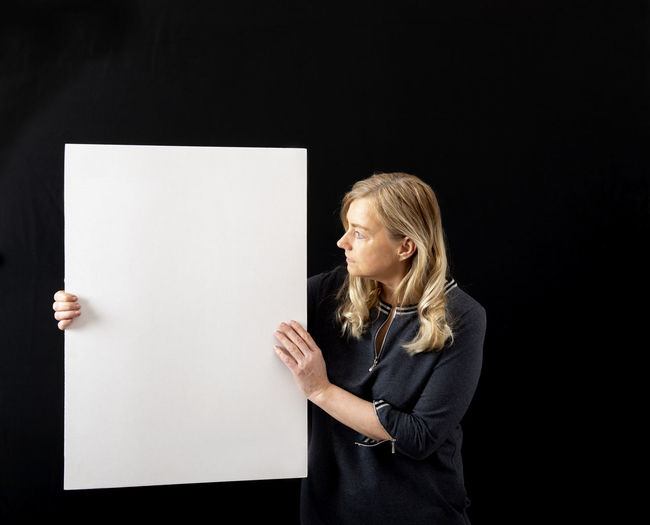 Mid adult woman standing against black background