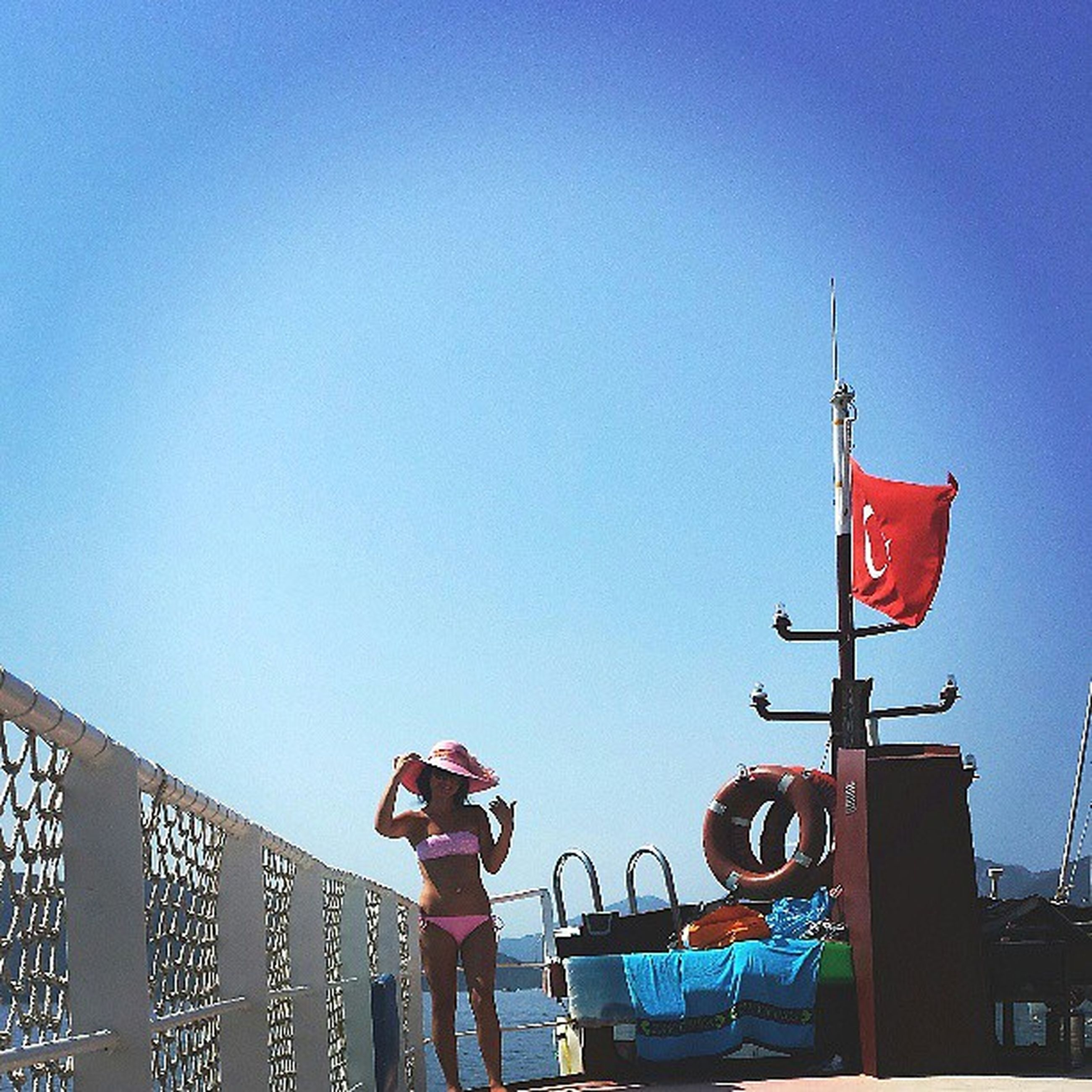 clear sky, copy space, blue, low angle view, red, leisure activity, lifestyles, men, flag, built structure, outdoors, standing, day, sky, travel, nautical vessel, person, amusement park