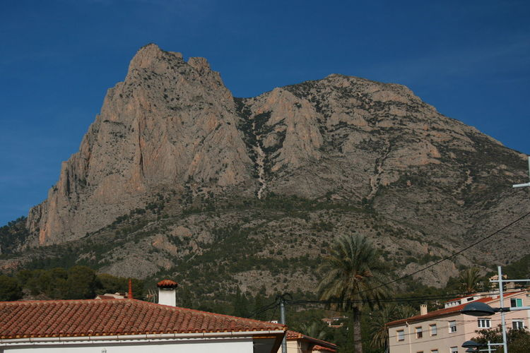 Low Angle View Of House And Mountains Against Clear Sky