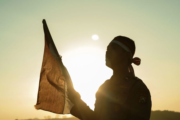 Silhouette man holding flag against clear sky during sunset
