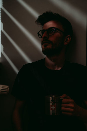 Young man having coffee and enjoying sunbeam through curtains.