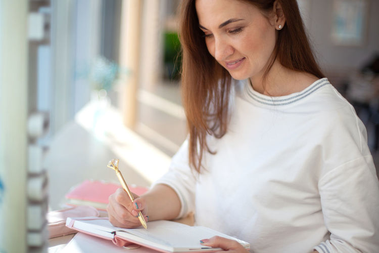 Midsection of woman holding paper while sitting on floor