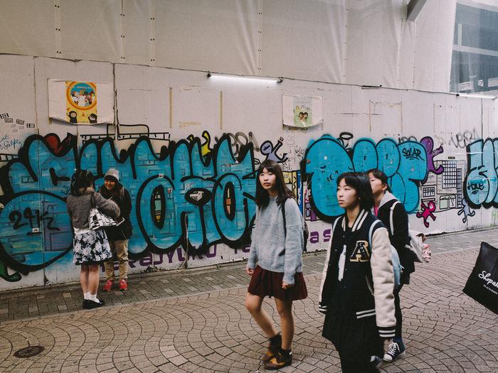 People walking on graffiti wall