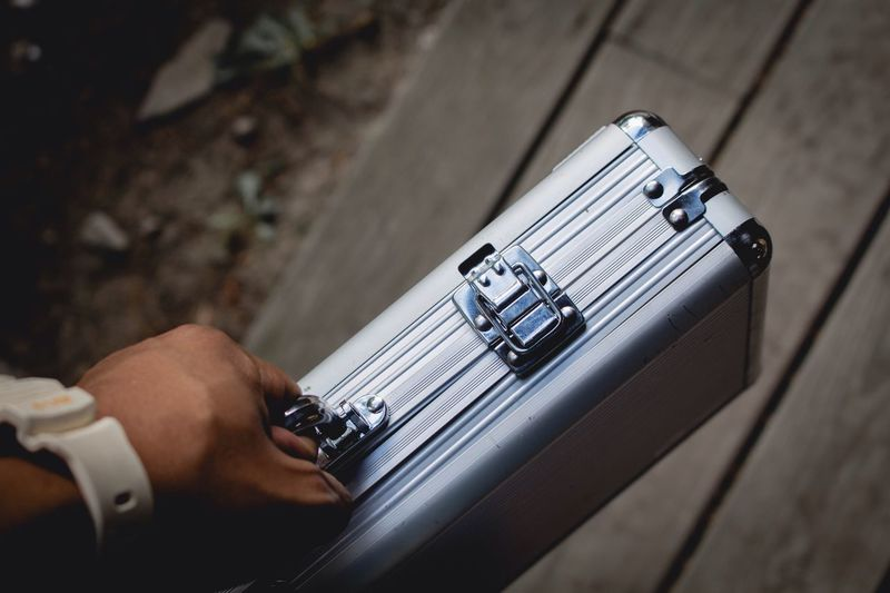 Cropped image of hand holding suitcase