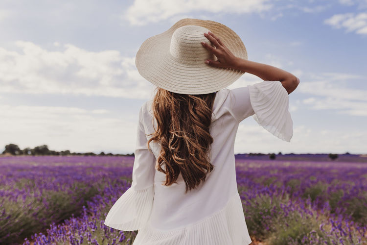 charming Young woman with a hat and white dress in a purple lavender field at sunset. LIfestyle outdoors. Back view Sunset Meadow Beauty Joy Leisure Freedom Farm Herbal Field Smile Charming Beautiful France Summer Lavender Purple Flower Enjoying Girl Walking Floral Happiness Natural Hat Woman Spring Cheerful Violet Lifestyles Sunny Bloom Passion Aroma Positivity Nature Young Relax Lady Expressing Provence Travel Tenderness Happy Outdoors Harmony Relaxation Blond Caucasian Lifestyle White Dress