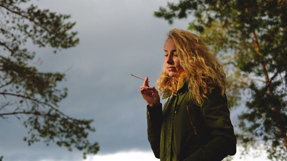 EyeEmNewHere MaksimovFoto Cigarette  Smoking Issues One Person Bad Habit Tree Smoking - Activity Addiction Outdoors Real People Leisure Activity Long Hair Holding Sky Young Adult Winter Nature Blond Hair Day Young Women Beautiful Woman