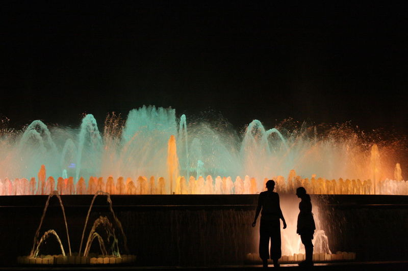 Two women standing in front of a fountain in Plaza España Barcelona Dark Event Flowing Water Fountain Illuminated Long Exposure Motion Multi Colored Night Outdoors Shadow Standing Water Water Play
