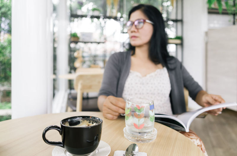 Woman Looking Away While Sitting At Table In Cafe