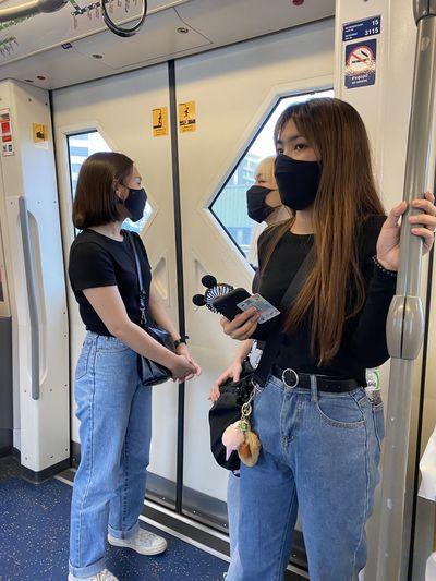 Women wearing masks standing in subway train