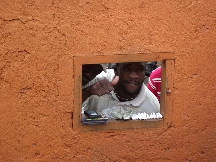 Man showing thumbs up seen through window