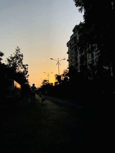 Street by silhouette buildings against sky at sunset