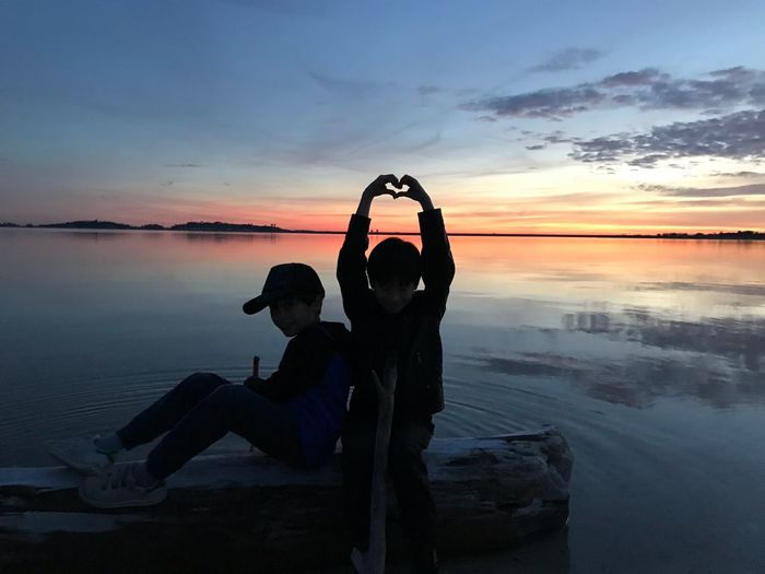 Silhouette boy making heart shape by friend sitting on driftwood at beach during sunset