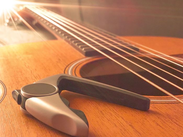 Acoustic guitar and capo Capo String Instrument Musical Instrument Music Musical Equipment Arts Culture And Entertainment Indoors  Musical Instrument String Guitar No People Still Life Close-up String Wood - Material Acoustic Guitar High Angle View Focus On Foreground Sunlight