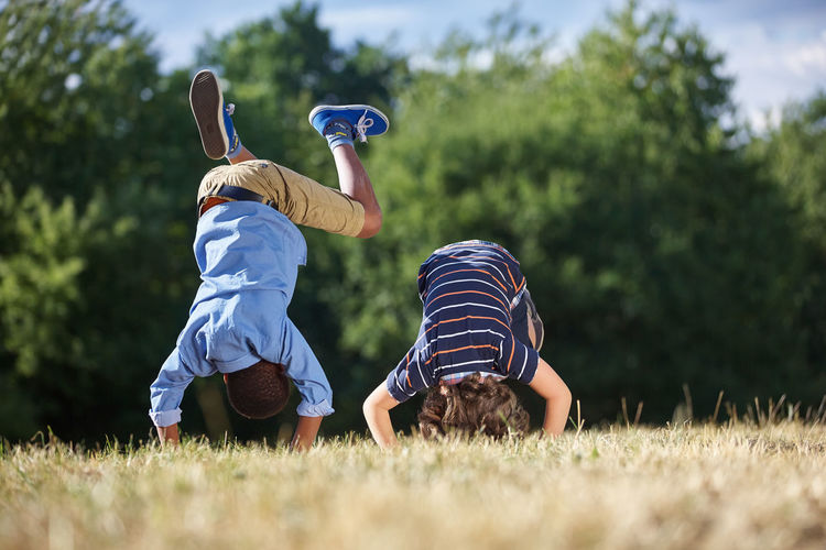 Rear view of male friends practicing handstand at park