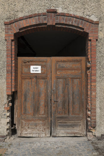Old Gateway of running down building in the sunshine Entrance Gate Arch Architecture Brick Building Building Exterior Built Structure Closed Closed Door Communication Day Door Entrance No People Outdoors Running Down Safety Security Sign Text Timber Two-wing Door Wall Wood - Material Wooden Texture