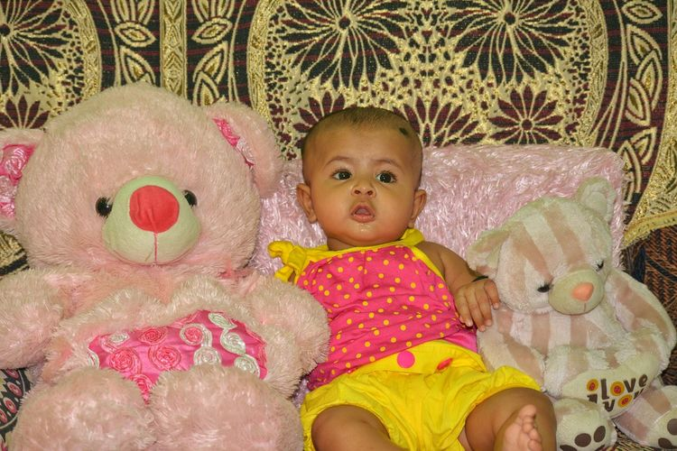 Cute Baby Girl Lying By Teddy Bear On Sofa At Home