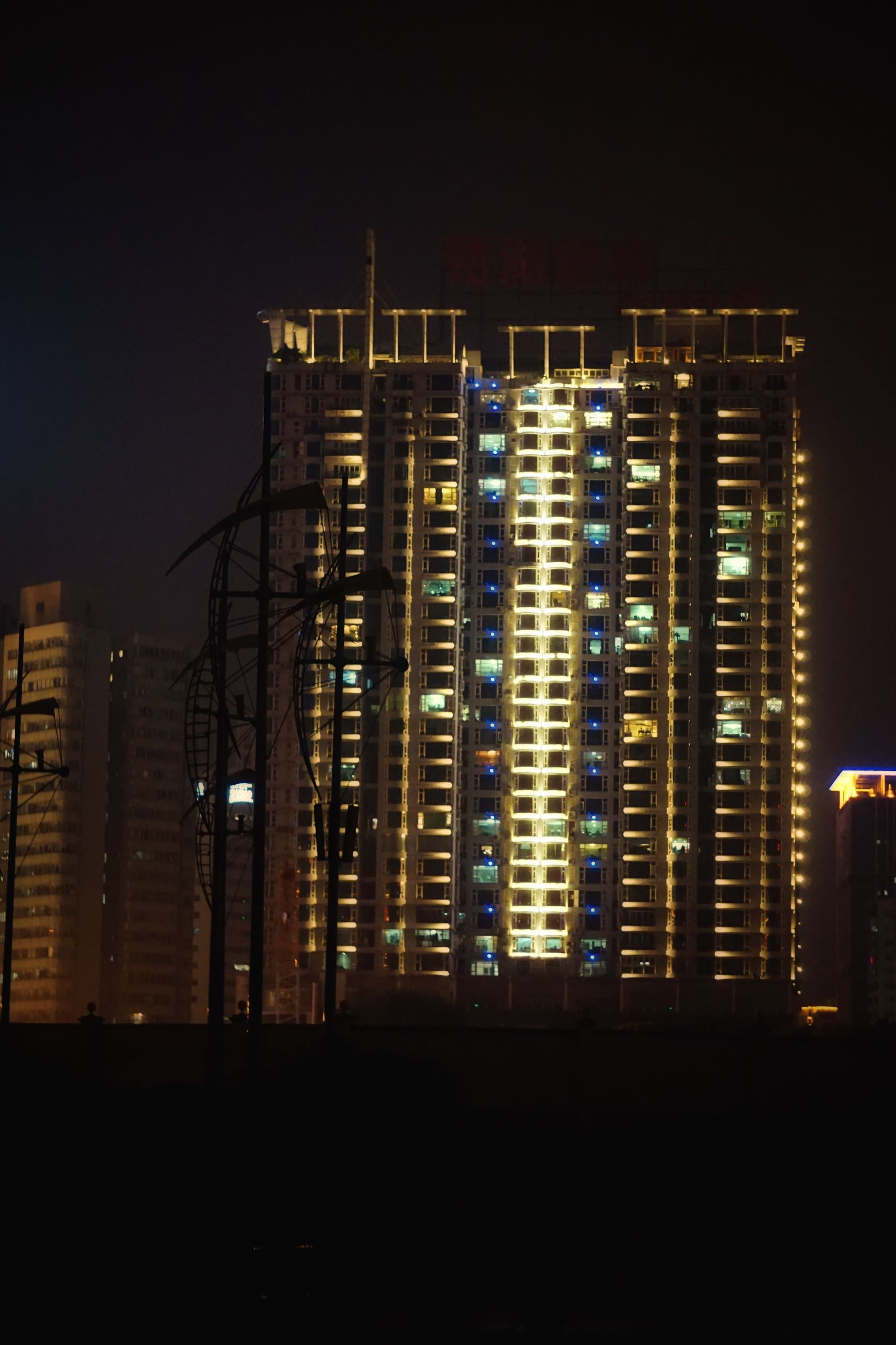 architecture, building exterior, built structure, city, skyscraper, tall - high, tower, building story, night, development, illuminated, residential building, apartment, travel destinations, city life, urban skyline, wide shot, wide, sky, office building, glowing, modern, romantic sky, growth, outdoors, residential district, tall
