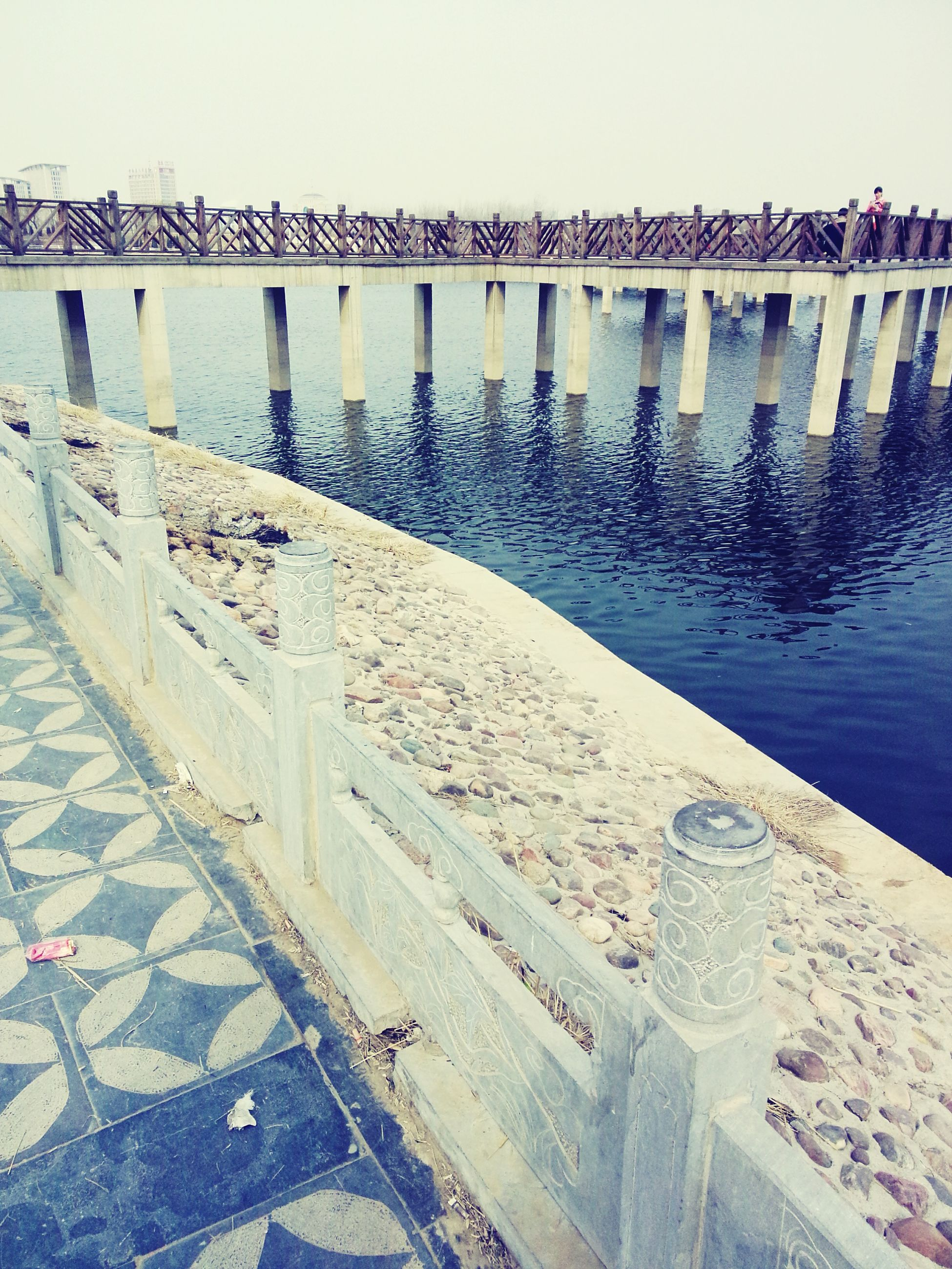 water, built structure, architecture, clear sky, building exterior, pier, river, day, bridge - man made structure, sea, railing, high angle view, outdoors, transportation, lake, no people, connection, in a row, nature, waterfront