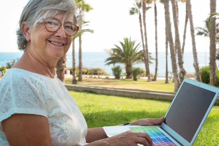 Portrait of smiling woman using laptop in park
