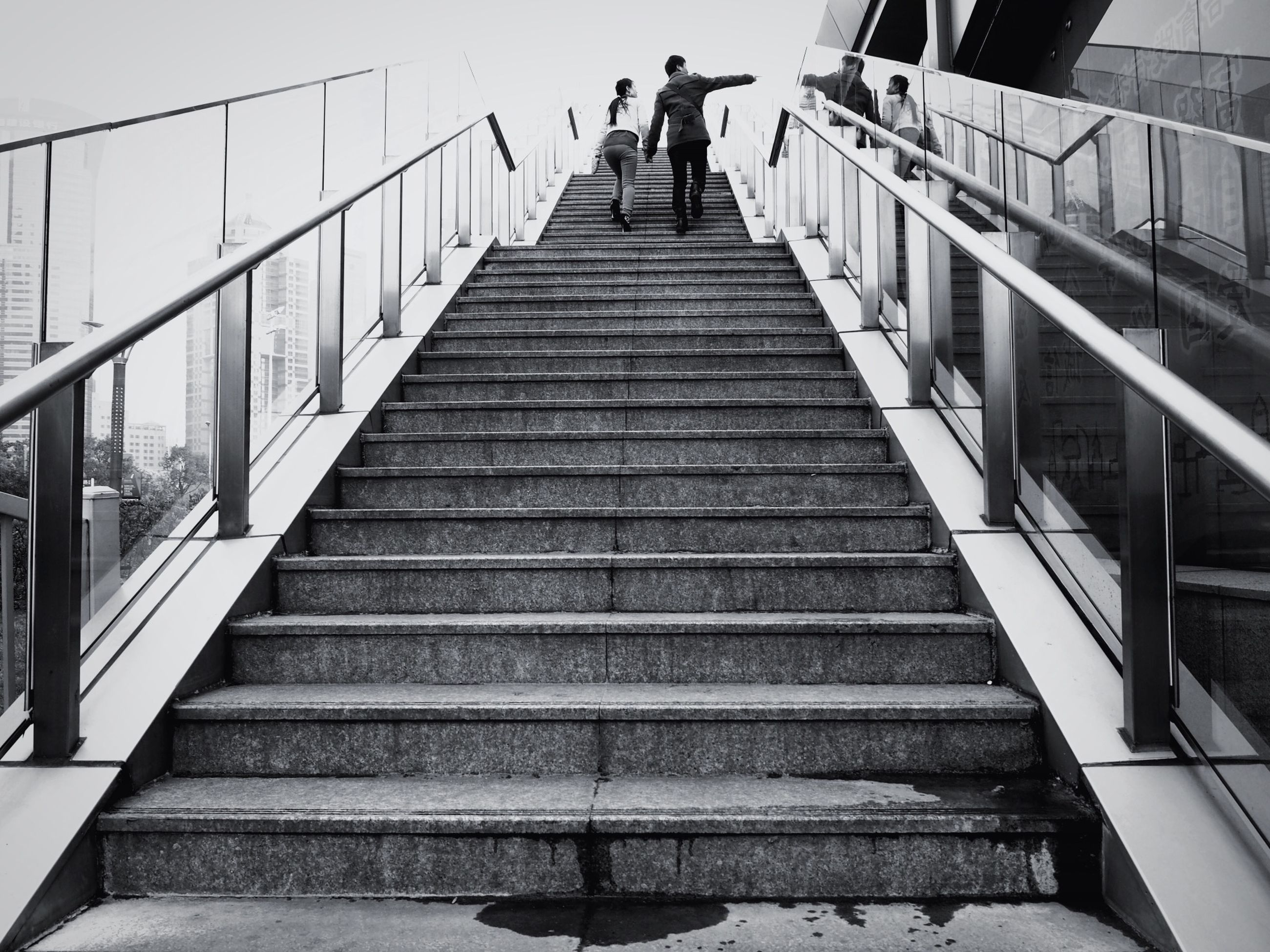 steps, steps and staircases, staircase, railing, men, architecture, built structure, the way forward, lifestyles, walking, stairs, low angle view, person, leisure activity, full length, moving up, building exterior, diminishing perspective