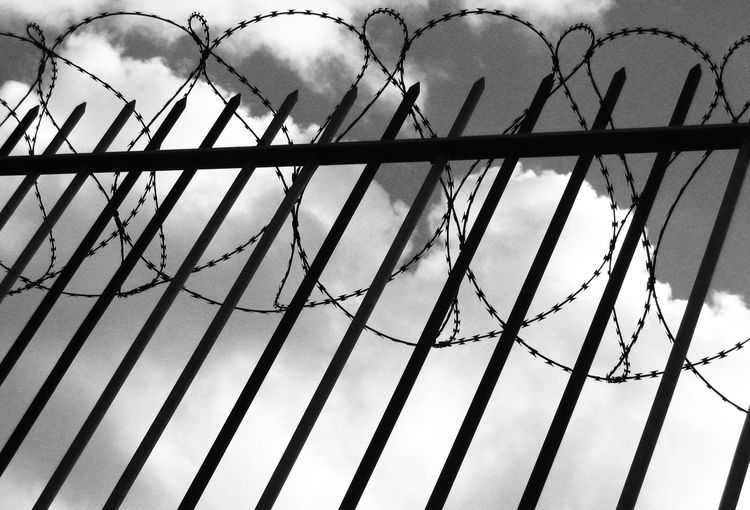 Low angle view of fence against sky