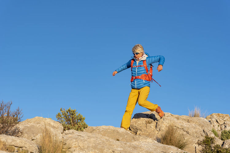 Low angle view of boy climbing against clear blue sky
