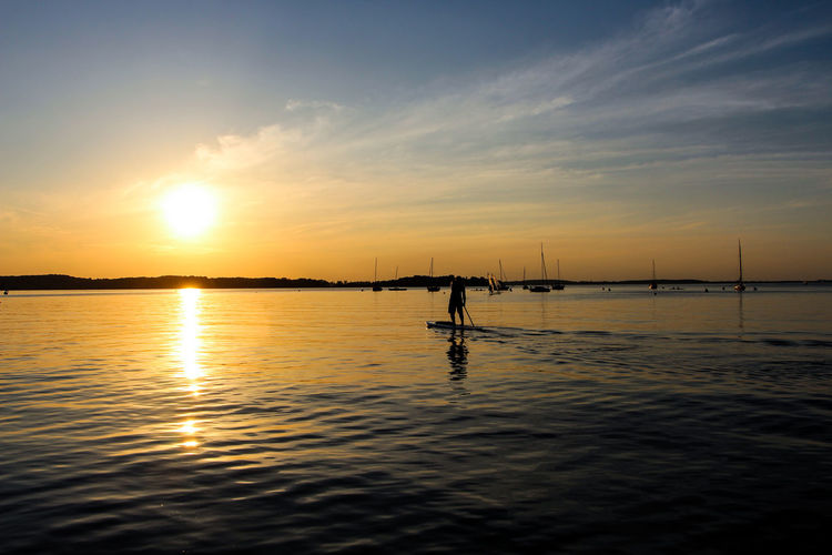 Rear view of silhouette man paddleboarding on lake against orange sky